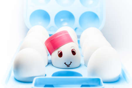 Egg with a smile and bunny teeth and a pink cap in a blue egg tray photo