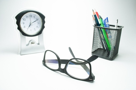 rimmed: glasses table clock and pen stand Stock Photo