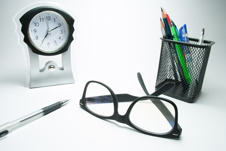 rimmed: glasses table clock and pen stand on white