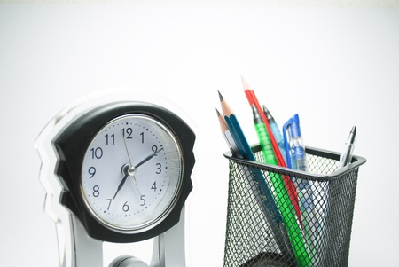table clock and pen stand on white photo