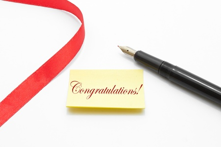 Congratulations written on a note paper with a pen beside it and decorated with a red lace