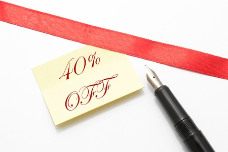 a sticker note with fourty percent off written on it with an ink pen beside it photo