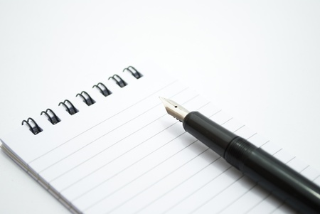 note pad and pen on white background photo