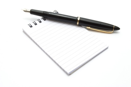 note pad and ink pen on white background photo
