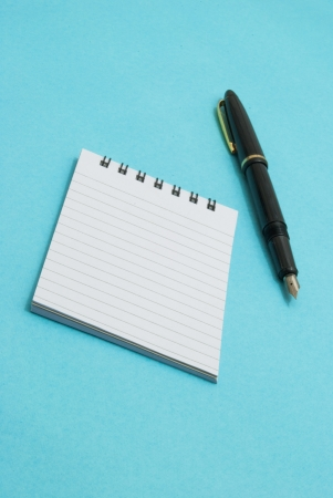 note pad and ink pen on blue background photo