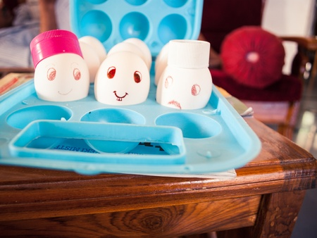 Egg with a smile and bunny teeth and cap in a blue egg tray photo