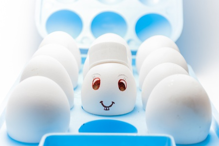 Egg with a smile and bunny teeth and a cap in a blue egg tray photo