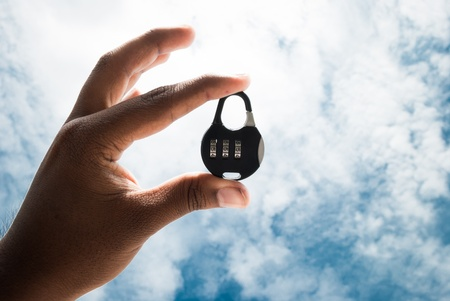 number lock held in hand on blue bright sky background Stock Photo