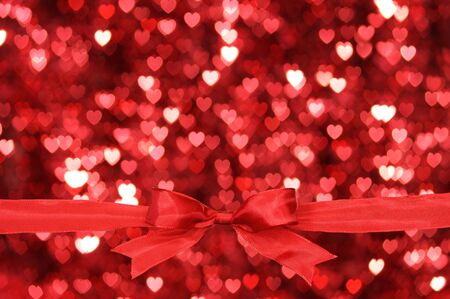 Red ribbon and heart shaped blurry pattern background. photo