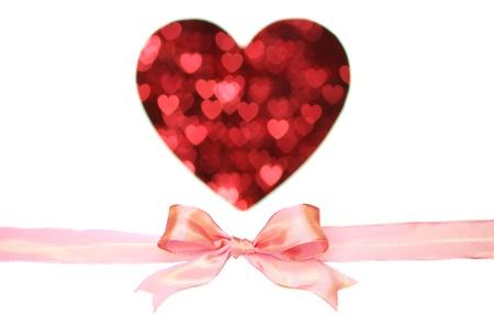 ピンクのリボンとハート形の白い背景の上のぼやけたパターン。