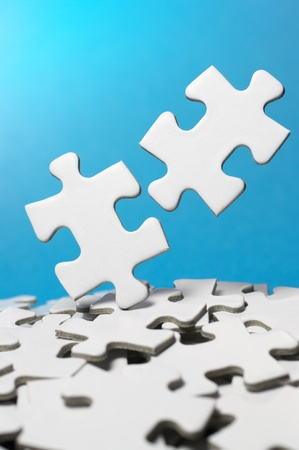 Trying to fit two jigsaw puzzle pieces  vertical Stock Photo - 13105328