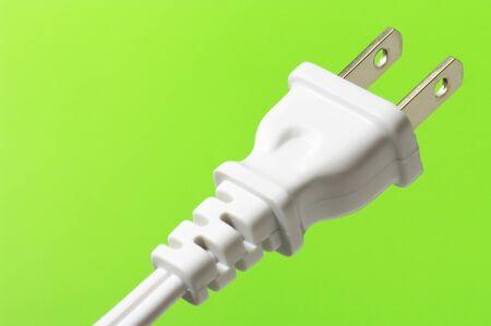 electric plug: white electric plug on green background (horizontal)