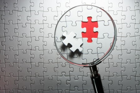 Search for missing puzzle pieces with a magnifying glass  photo