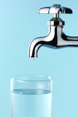 Glass of water and tap with drop.