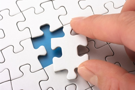 A person fitting the last puzzle piece Concept image of building and button up