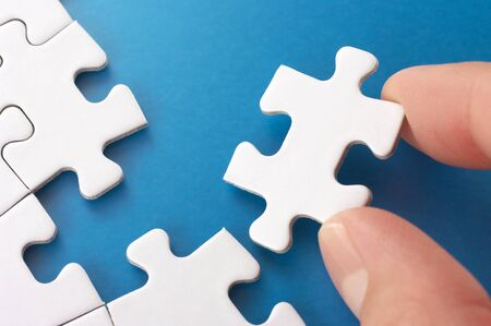 A person assembling puzzle pieces Concept image of building and growth Stock Photo - 18013004