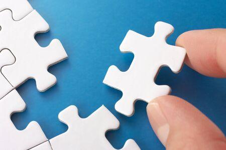 jigsaws: Una persona montaggio pezzi del puzzle Immagine di concetto di costruzione e crescita