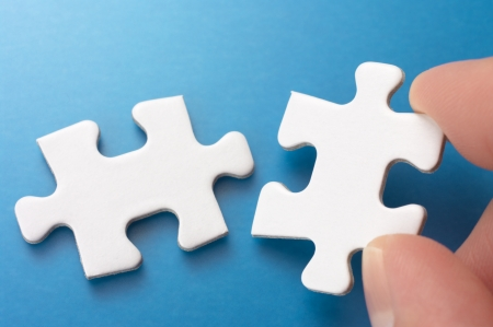 A person connecting two puzzle pieces Concept image of building