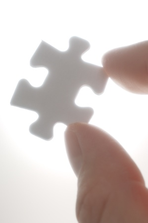 one piece: A person picking up one puzzle pieces against the light.(vertical)Soft focus photograph. Close-up of puzzle piece. Stock Photo