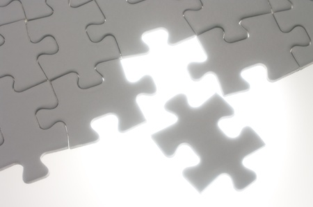 Assembling jigsaw puzzle pieces against the light.Soft focus photograph. Concept image of building. photo