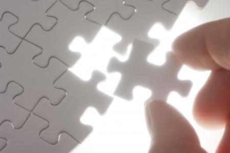 A person assembling puzzle pieces against the light.Soft focus photograph. Concept image of building. photo