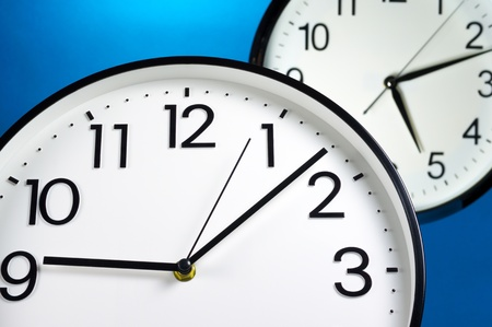 scheduled: Scheduled time Two wall clocks on blue background  Stock Photo