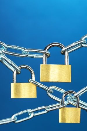 Strong security systems  Close up of padlocks and chain on blue background   vertical Stock Photo - 21999359