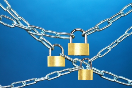 Strong security systems  Close up of padlocks and chain on blue background  Stock Photo