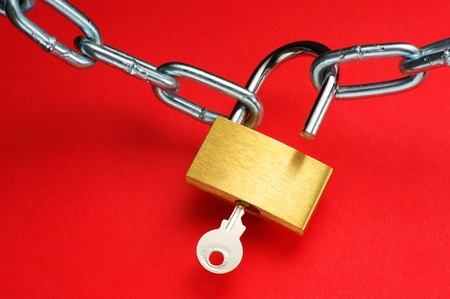 Unlocking padlock and chain on red background