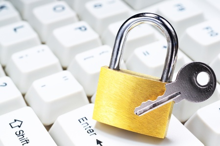 Secure computer from cyber crime  Close up of padlock and key on keyboard  Stock Photo - 21999369