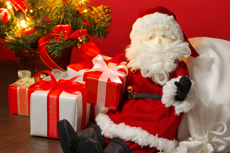 sackful: Sitting down stuffed toy Santa Claus, many presents and Christmas tree