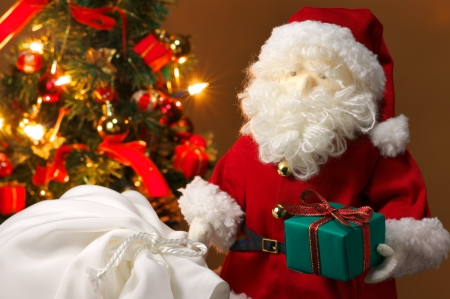 Stuffed toy Santa Claus, a bag of presents and Christmas tree   horizontal  photo