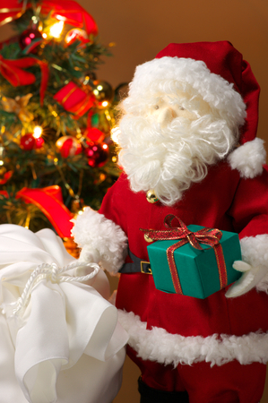 Stuffed toy Santa Claus, a bag of presents and Christmas tree   vertical  photo