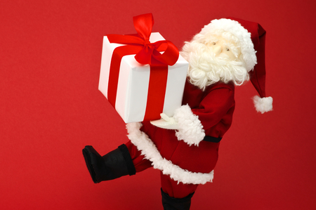 plushie: Stuffed toy Santa Claus carrying present on red background