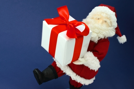 plushie: Stuffed toy Santa Claus carrying present on dark blue background
