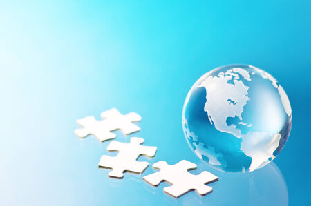 Glass globe and jigsaw puzzle pieces Building global business  photo