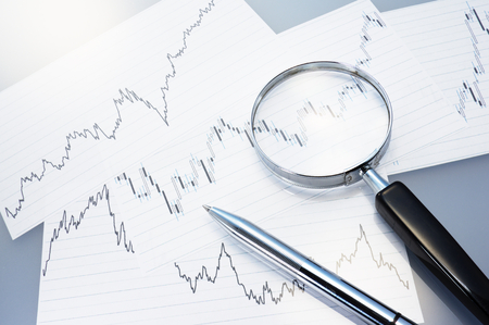 fluctuation: Charts, magnifier and pen  Analyzing exchange fluctuation  Stock Photo