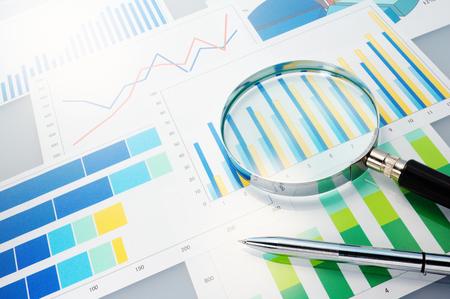Graphs, magnifier and pen  Analyzing finances  Archivio Fotografico