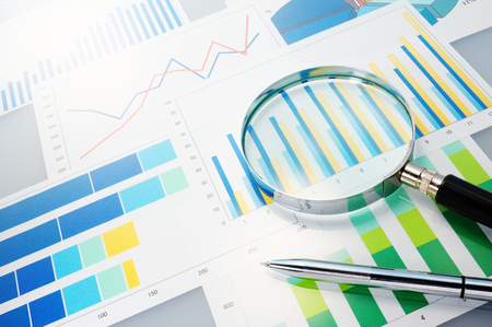 magnifying glass: Graphs, magnifier and pen  Analyzing finances  Stock Photo