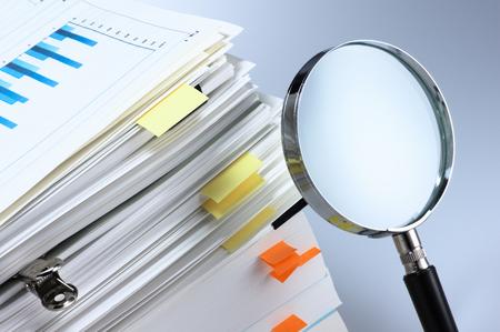 documentos: Investigar y analizar Lupa y pila de documentos Foto de archivo