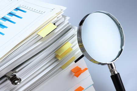 Investigate and analyze  Magnifying glass and stack of documents  photo