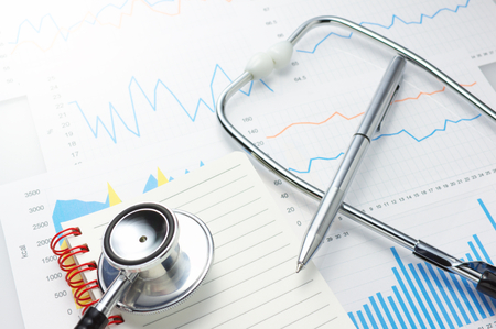 Investigation of daily health conditions  Close up of graphs, stethoscope, notebook and pen