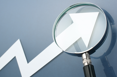 Looking upside growth arrow with magnifying glass.Concept image of growth potential. White arrow and magnifying glass on dark blue background. Stockfoto