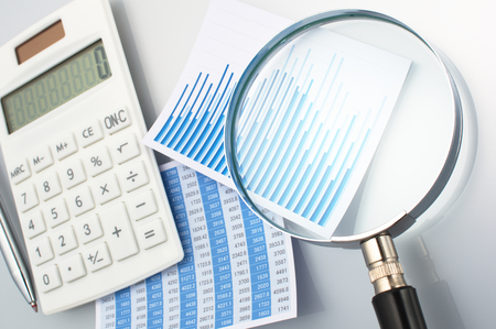 graphing: Looking graph with magnifying glass. Calculating and graphing and analyzing data. Graph chart magnifying glass and calculator on gray background.