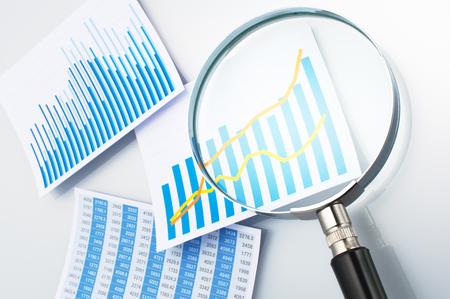 lupa: Investigar y lectura de datos con lupa. Tres gráficos y lupa sobre fondo gris.