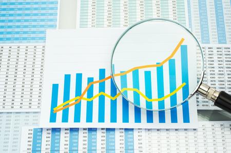 多くのチャート グラフと虫眼鏡。データを分析します。虫眼鏡でグラフをチェックします。