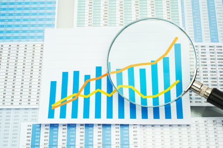 Many charts graph and magnifying glass. Analyzing data. Checking graph with magnifying glass. Stockfoto