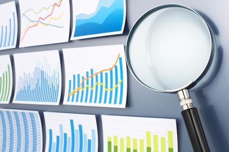 lupa: Investigar y analizar los datos con lupa. Encuesta de tendencia. Muchos gráficos y lupa sobre fondo azul oscuro.