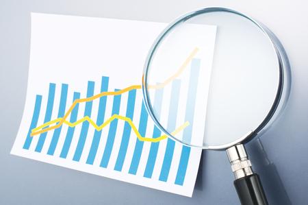 虫眼鏡を使用してデータの分析、調査です。グラフと灰色の背景に虫眼鏡。データを読み込んでいます.