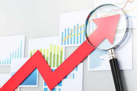 Looking upside growth arrow with magnifying glass. Graphs and data confirming growth. Red arrow and magnifying glass on the background of graphs and charts.